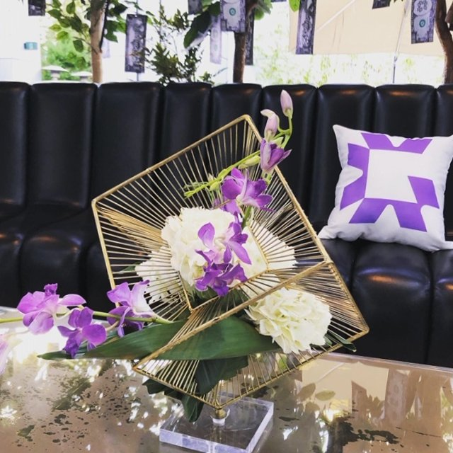 custom live flower arrangement in geometric shape statue with purple orchids and white hydrangea