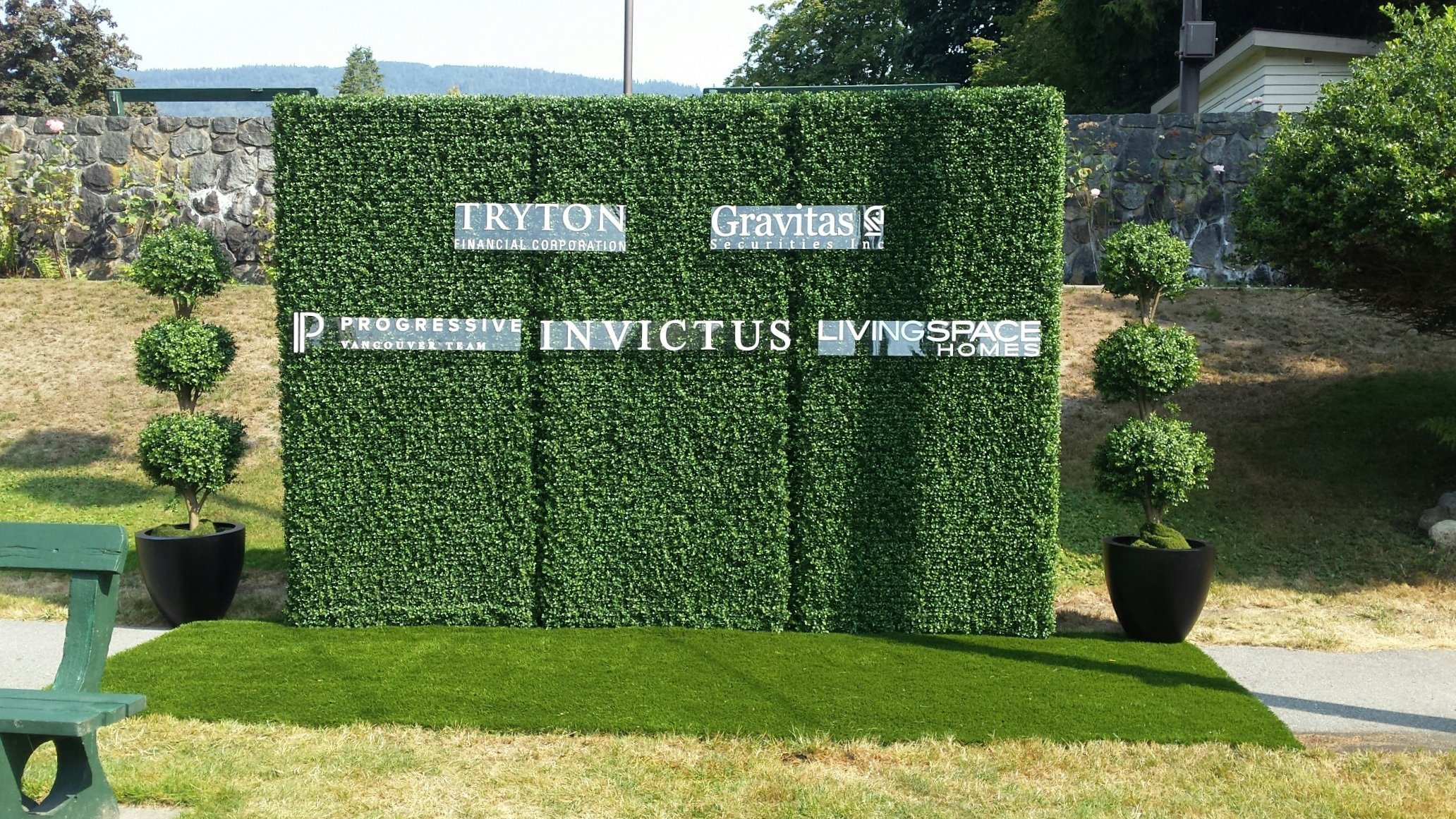 Boxwood hedge backdrop with custom printed logo decals on clear plexiglas backings, flanked by potted three ball topiaries and artificial turf