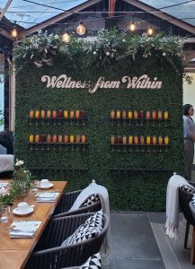 Boxwood self serve champagne wall with custom signage and live floral treatment for brand promotion event.