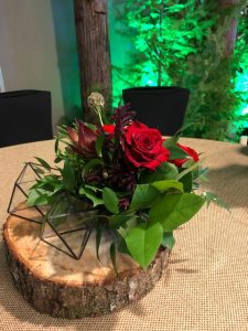 Geometric terrariums on top of wood tree cookie with red rose and salal live flower arrangement