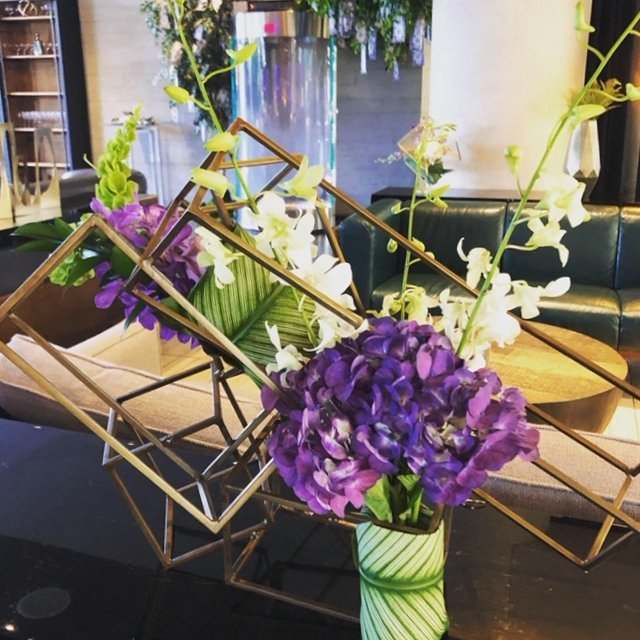 unique floral centrepiece for CCP Events in geometric shaped container, purple hydrangeas and white orchids