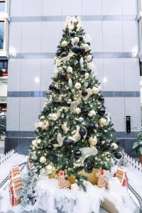 commercial christmas tree in office building lobby with black, white and gold decor