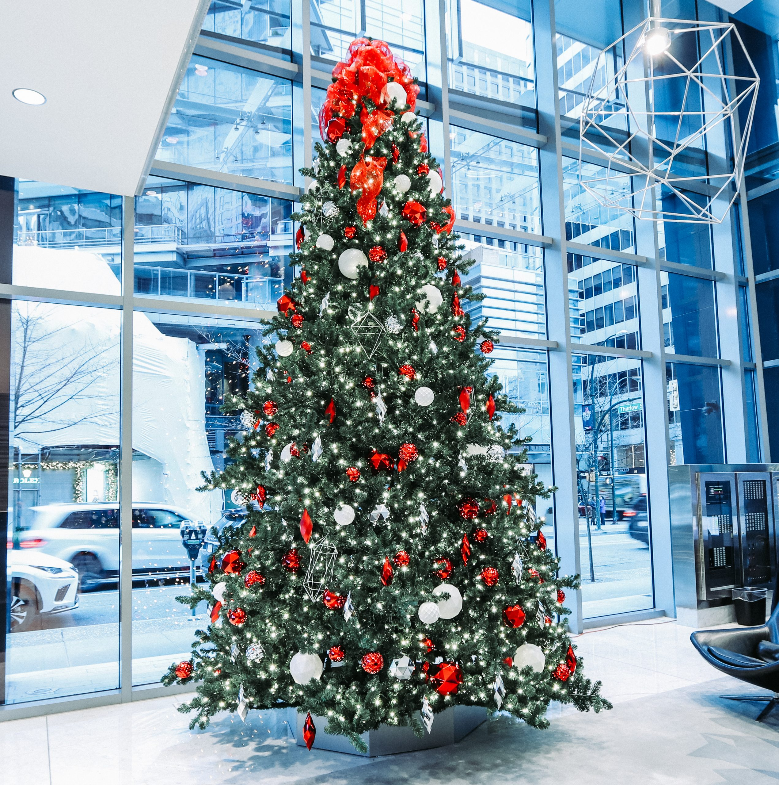 commercial christmas tree in office building lobby with red, white and silver decor, 16 feet tall