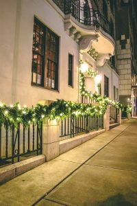 Exterior christmas decor of live and artificial mixed green garland with warm white LED lights on outside of restaurant building