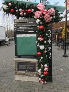 Shopping centre directory dressed in green garland with candy cane themed decor and bow accent