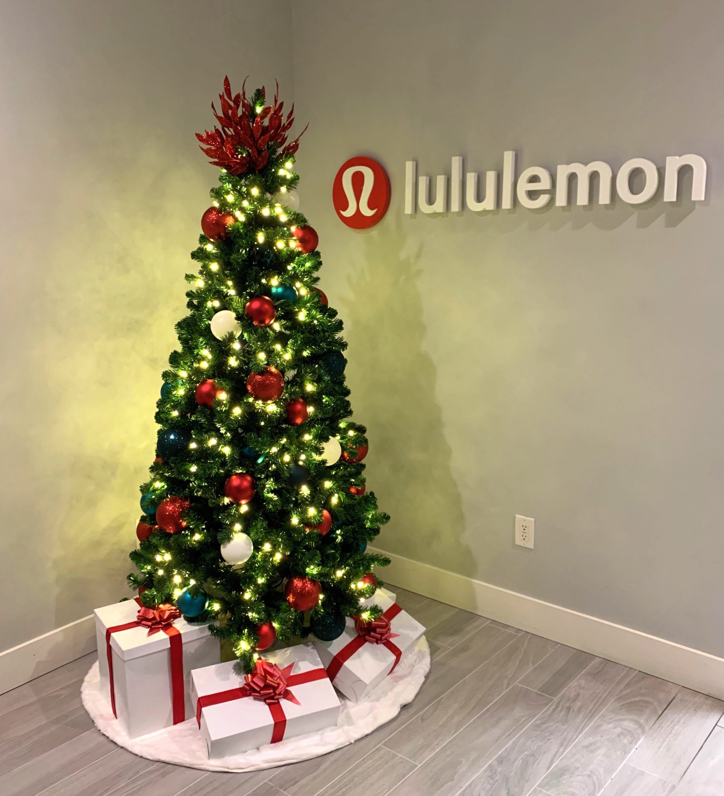 commercial christmas tree with brand colours red and white in office lobby