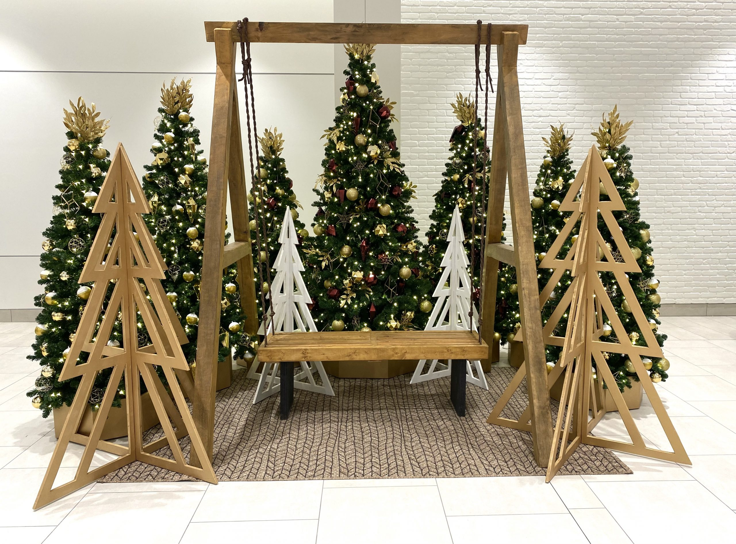 Custom wood swing set with 3D cut out trees and burgundy and gold decorated artificial christmas trees, photo op