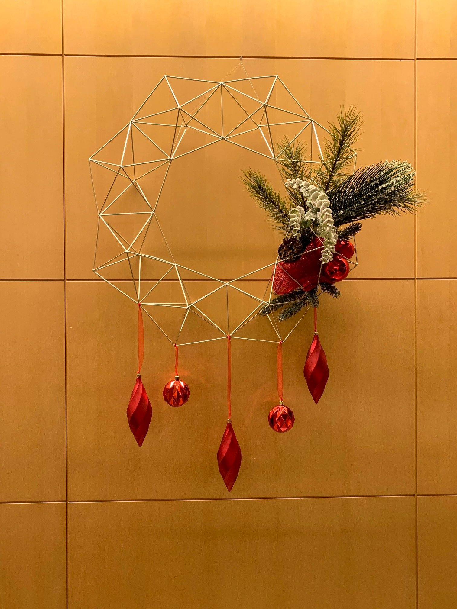 Wire geometric wreath with hanging red ornaments and green garland accent hanging on wood wall