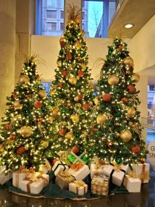 trio of commercial christmas trees decorated in gold, copper and emerald decor, present pile under trees
