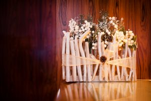 Gilded wood twig container with woodland inspired greenery as holiday centrepiece