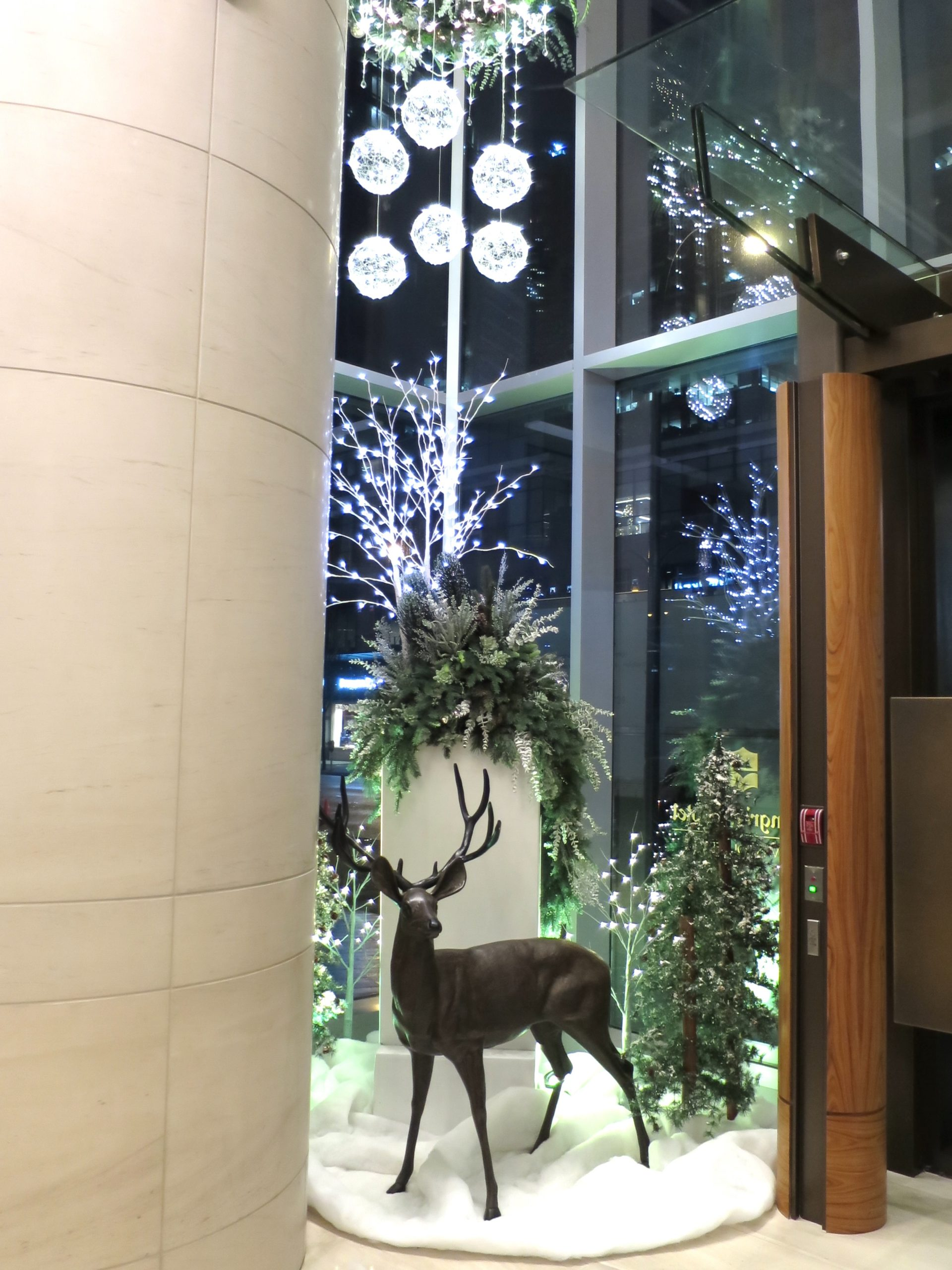 Custom Holiday window display at Shangri-La Hotel featuring large succulent and greenery planter, metal deer prop, alpine trees, snowblanket ground cover and custom wreath chandelier