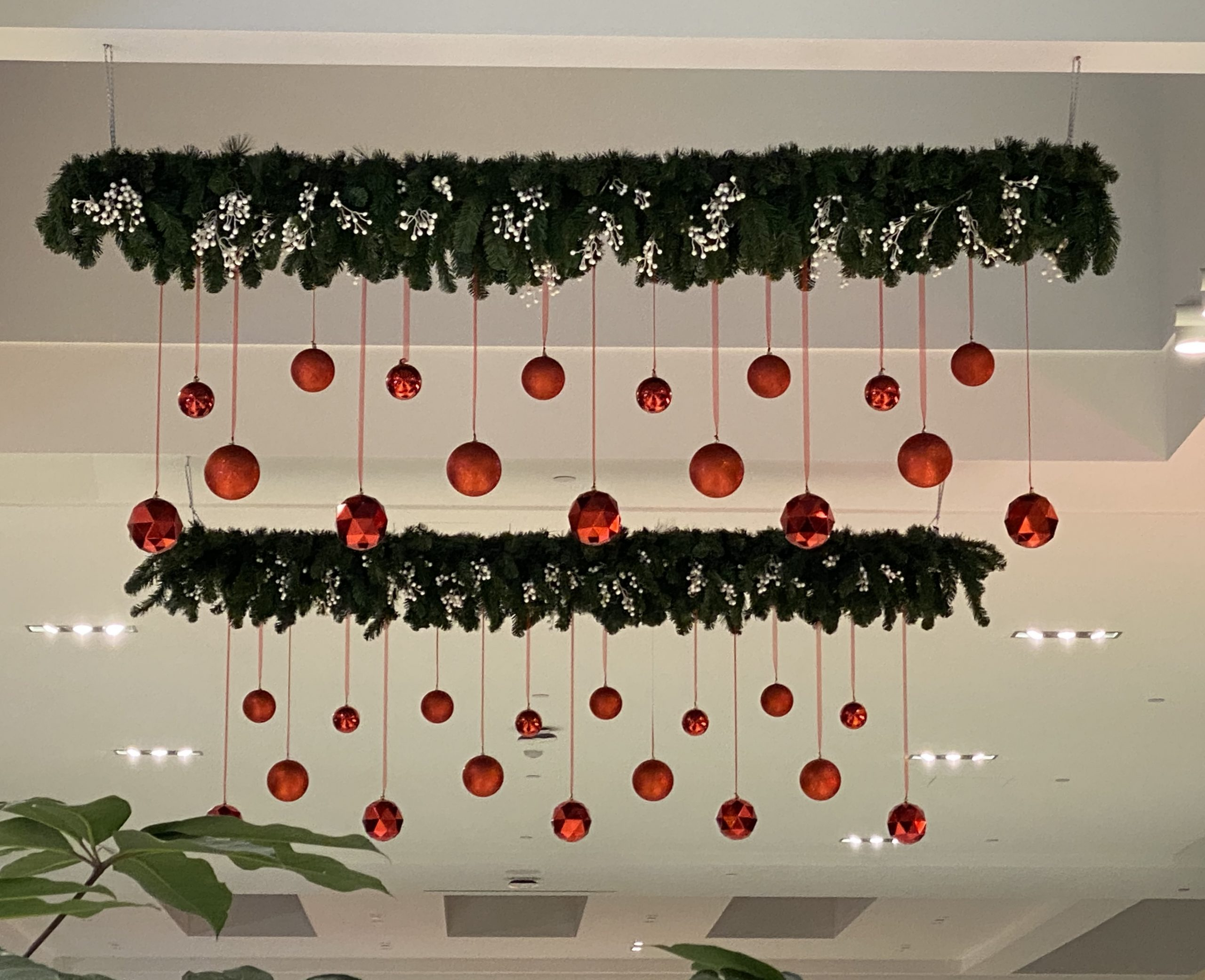 Hanging custom christmas garland with white berries and hanging red ornaments
