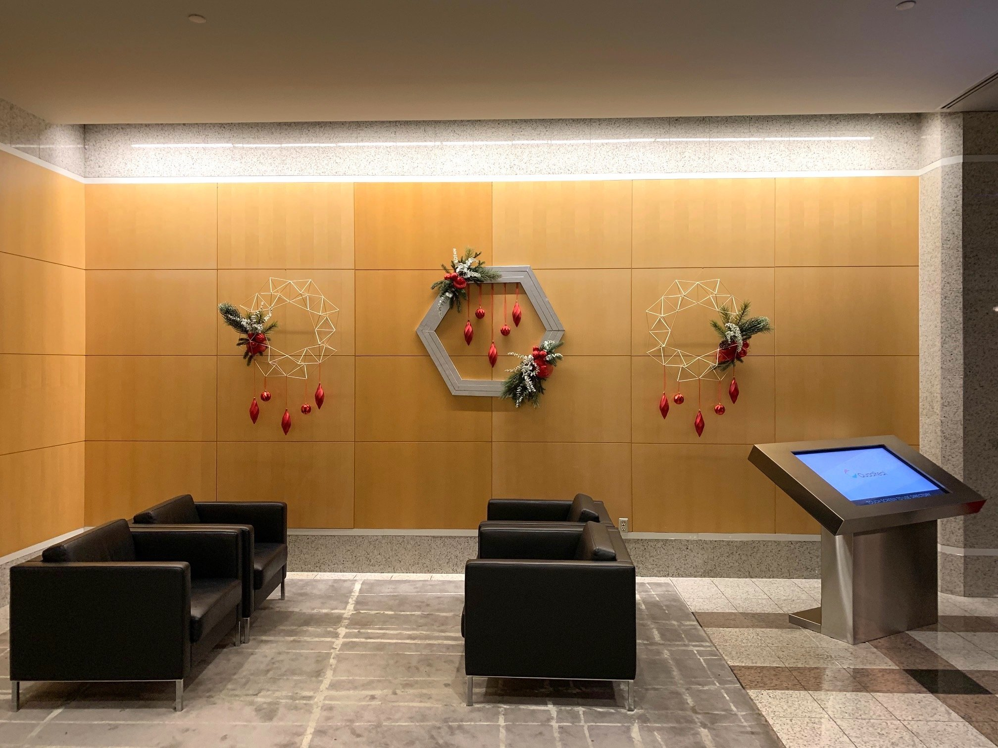 Two wire geometric wreaths flanking a custom wood hexagon wreath with hanging red ornaments and christmas greenery accents hanging on a wood wall in an office lobby