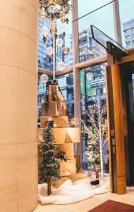 Hotel holiday window display with large gold wrapped present tower with black and gold accents, alpine trees and LED birch trees with custom wreath chandelier