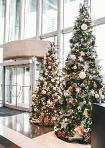 two varying height christmas trees in a winter woodsy decor theme with tree skirts and present pile under the trees in office lobby