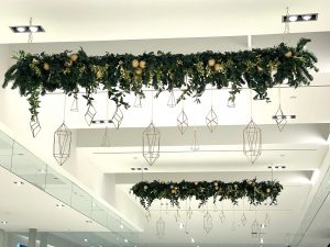 Overhead hanging decorative garland with hanging wire geometric ornaments, greenery accent and white berry decor