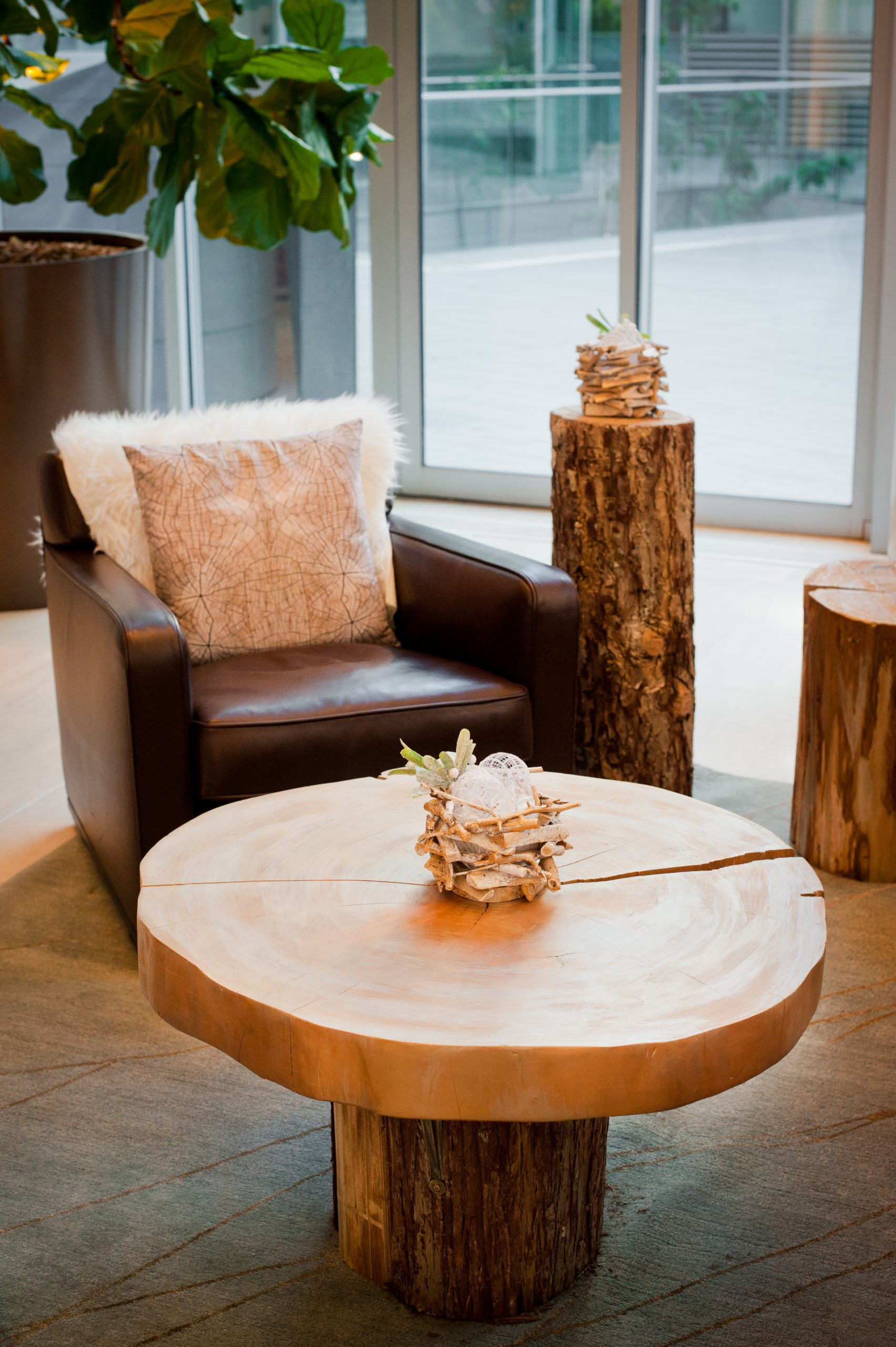 Hotel lobby accent decor with wood cookie and tree stump table, gilded woodland arrangement and west coast accents