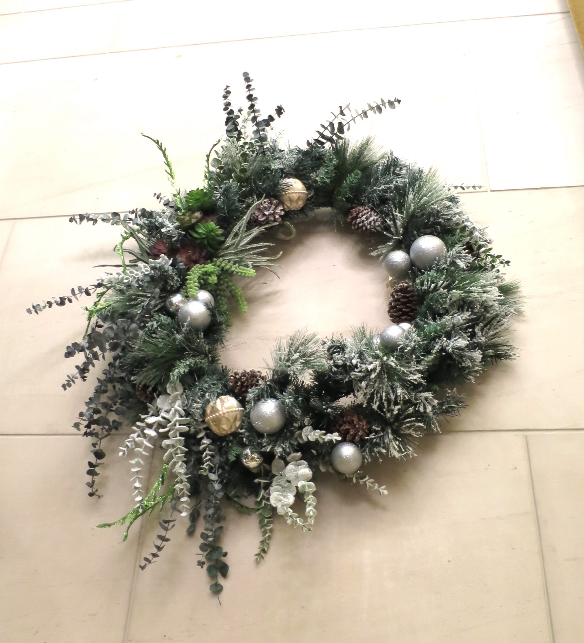 Christmas garland with succulents and evergreens and gold and silver ornaments hanging on a tile wall