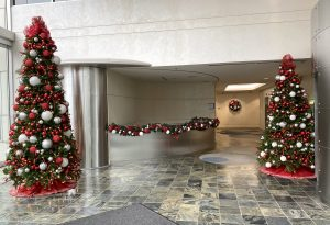 office lobby christmas decor with two christmas trees and decorated garland on lobby desk decorated with red white and silver decor