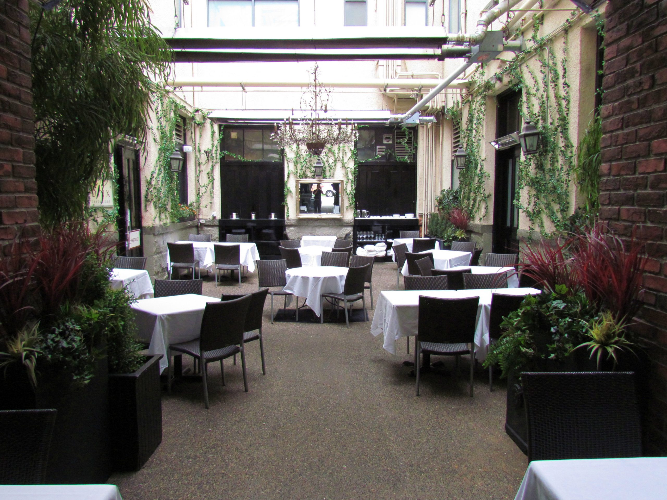 Covered patio decor at Brix and Mortar restaurant with custom potted artificial greenery