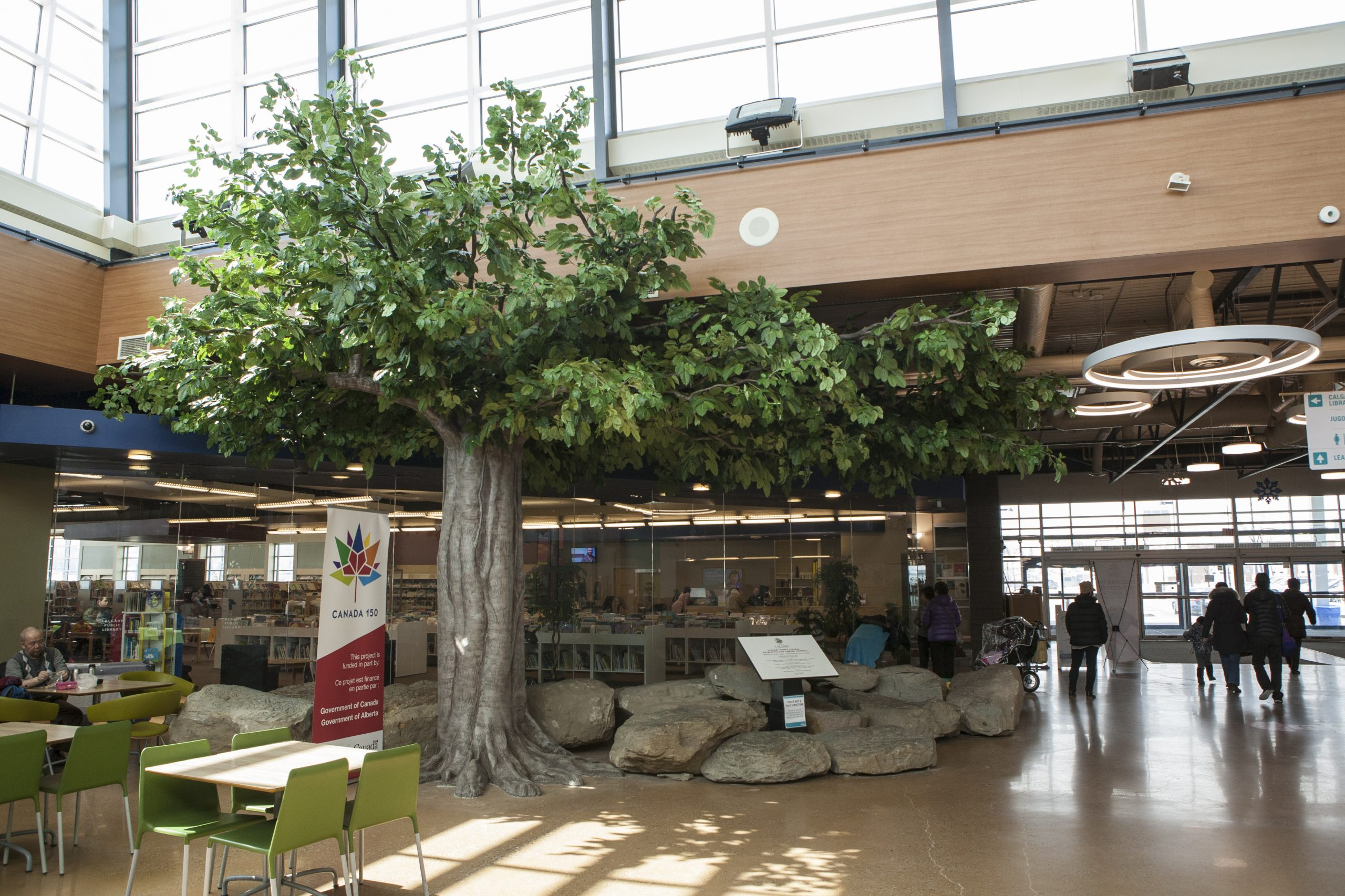 Oversized banyan tree with epoxy sculpted trunk as pillar wrap with 27' wide canopy at VIVO community centre
