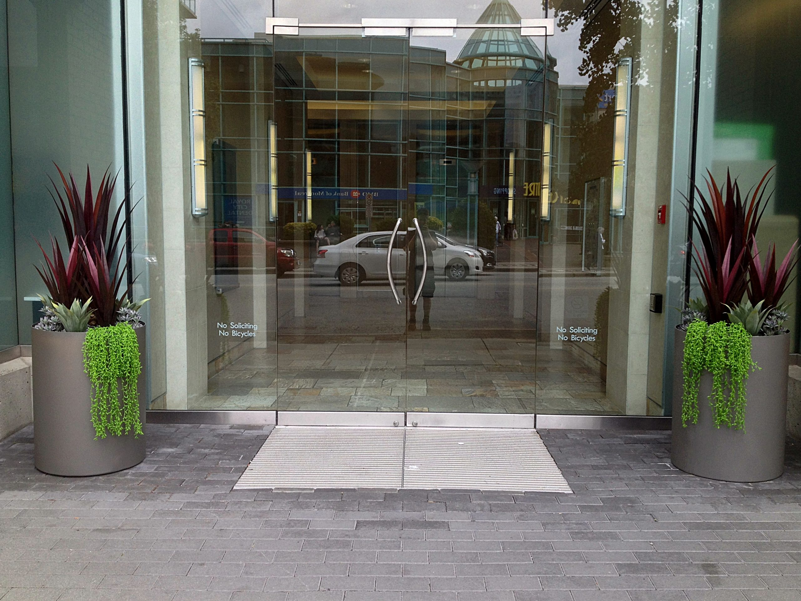 Uptown Properties, New West, outdoor office lobby commercial steel cylinder planters with artificial agave and succulents