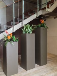 Artificial bromeliad and snake plant in custom tall steel tower planters