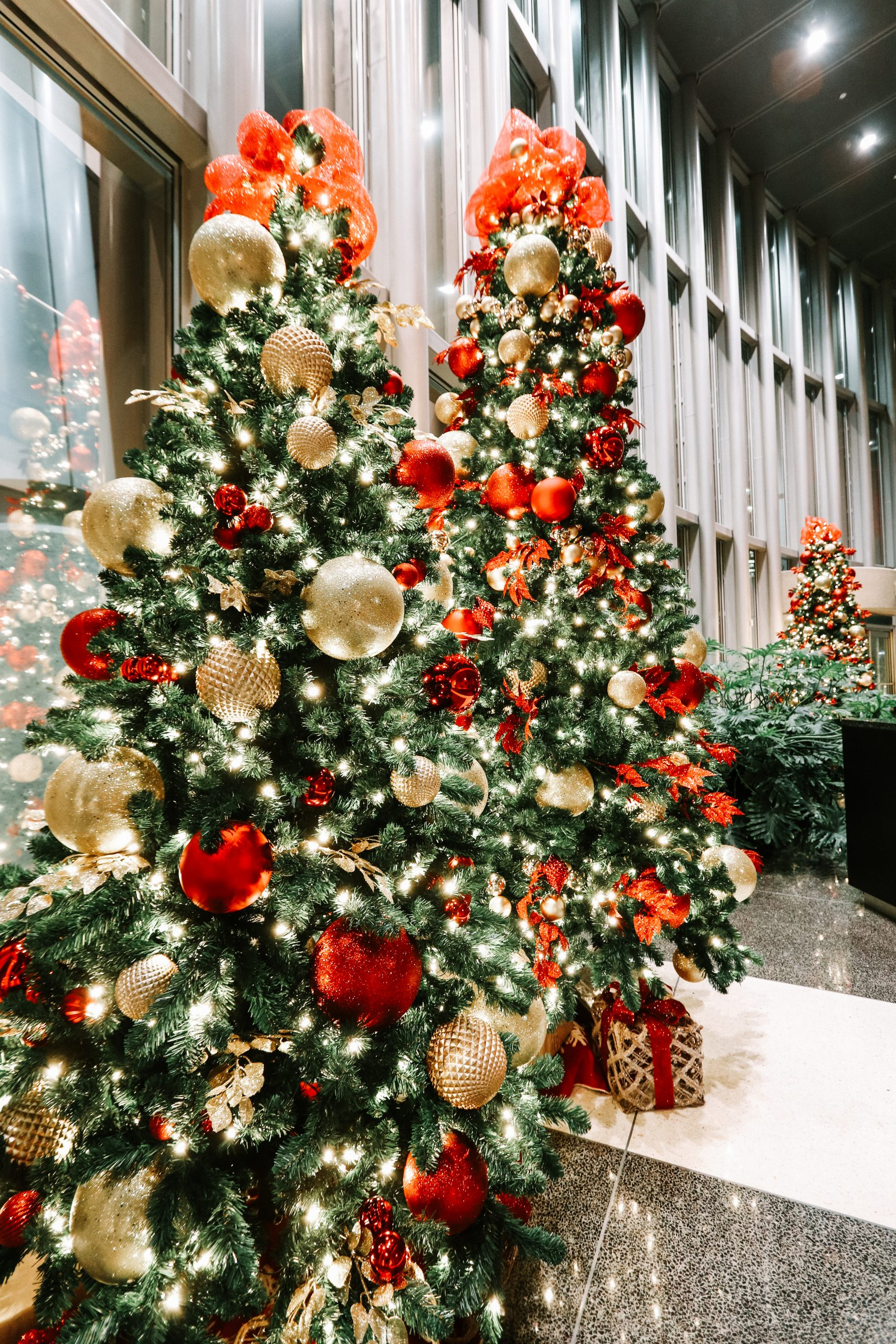 commercial christmas trees in office lobby decorated in traditional red and gold decor