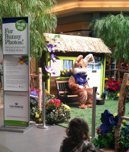 easter bunny set in shopping centre with tiki hut and park bench back drop, willow trees and floral ground cover