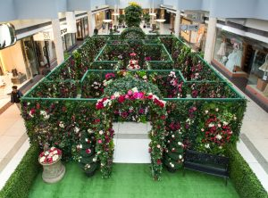 Secret garden maze made of lattice pieces dressed in greenery and pink flowers in the centre of Oakridge mall