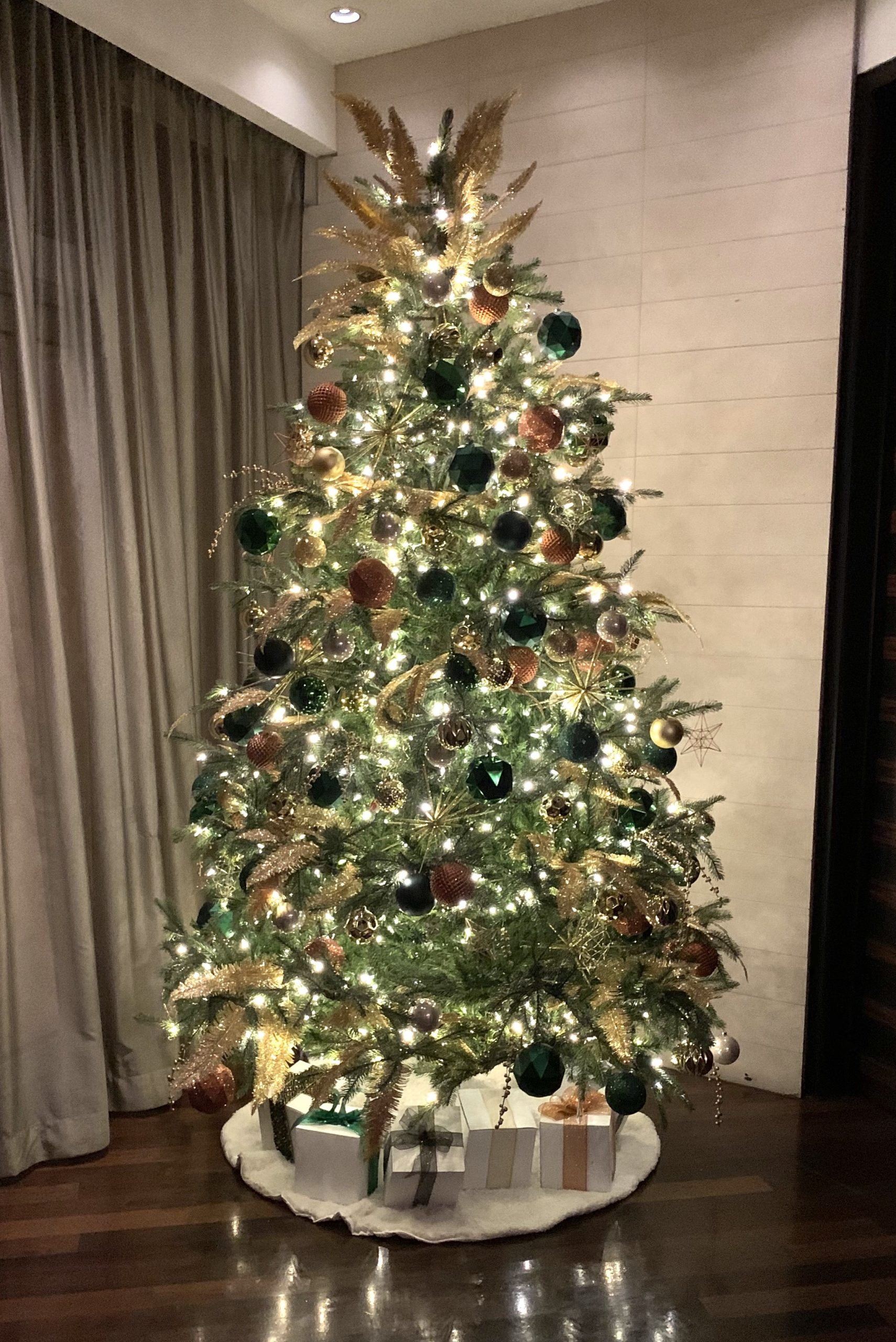 commercial christmas tree in hotel lobby decorated in emerald green, copper and gold geometric decor