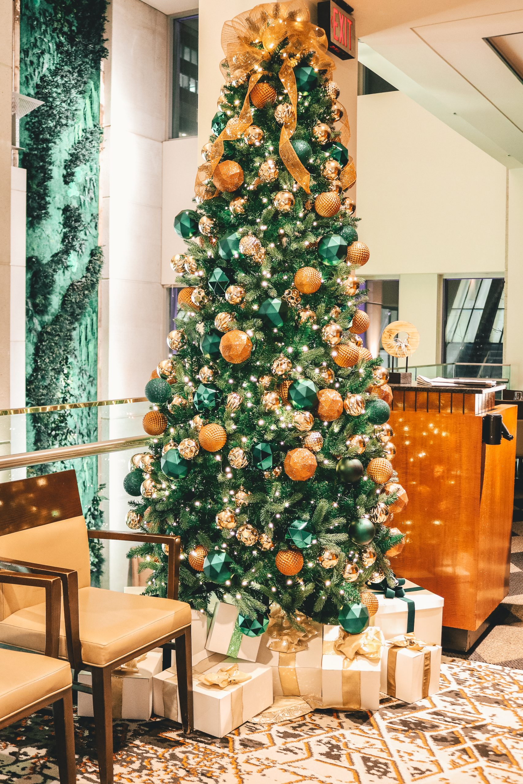 Emerald green and copper christmas tree with gold sinamay topper and white and gold present pile in hotel lobby