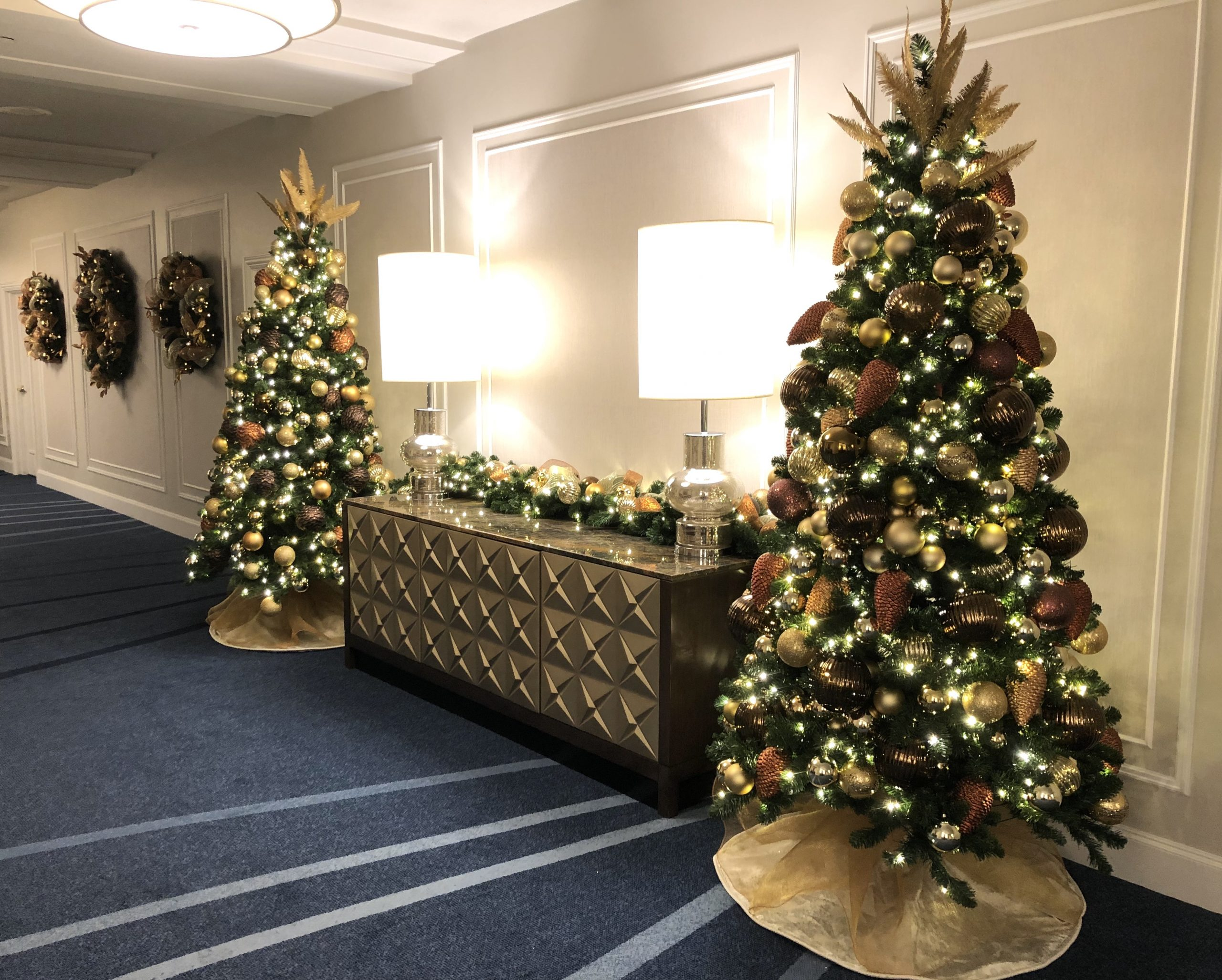 two commercial christmas trees decorated in mixed mtallic decor with tree skirts and decorated garland over credenza in hotel lobby