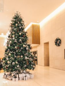 Shangri-La hotel lobby with 17' tall tree decorated in white black and burgundy decor with present pile and matching wreath on wall in background