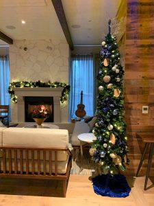 commercial pencil christmas tree decorated in navy blue and gold decor with blue tree skirt and matching garland on fireplace in background