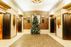 fairmont hotel vancouver lobby elevator bank christmas tree decorated in teal bronze and gold decor flanked with sconce swags