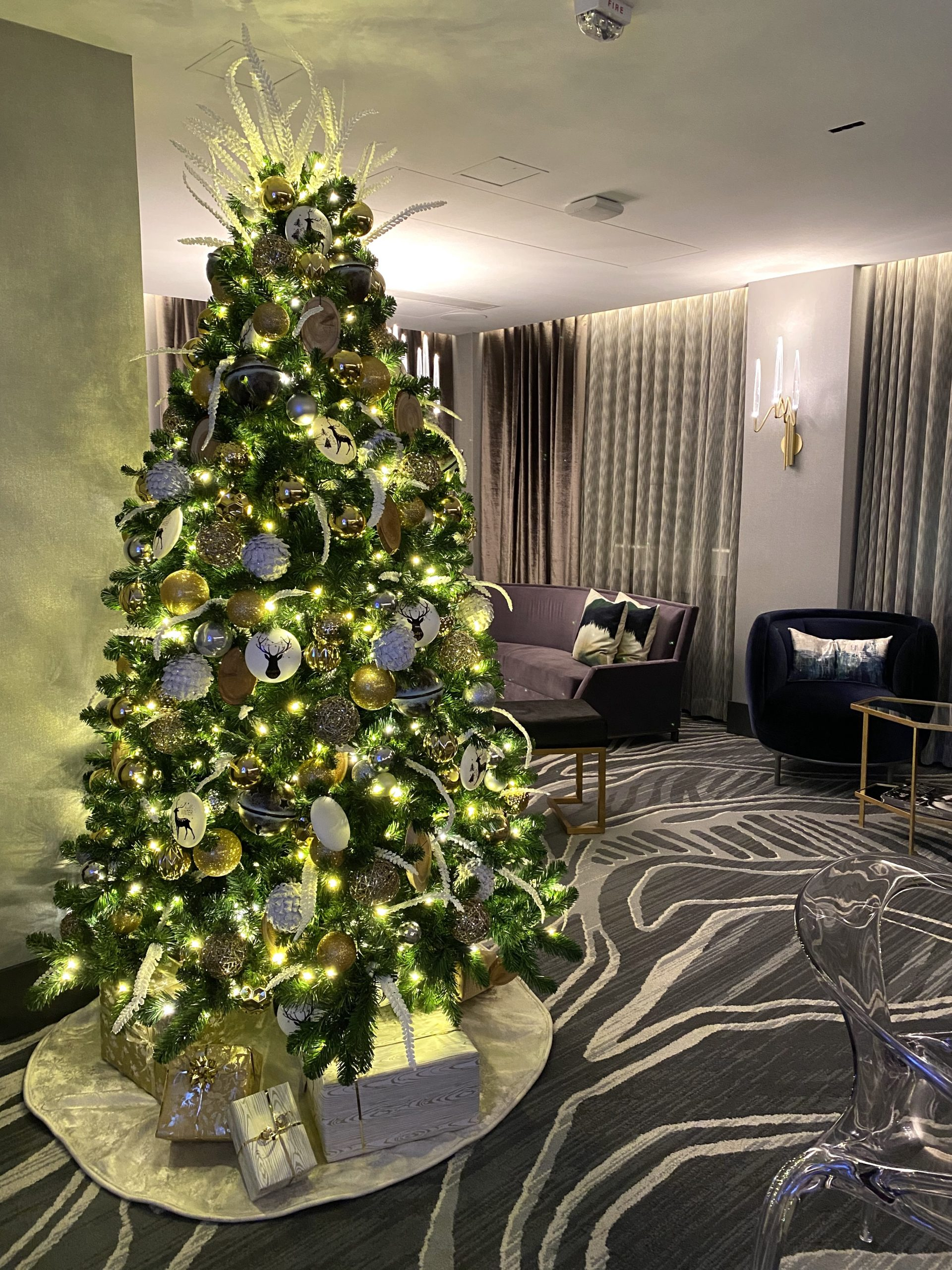 gilded west coast winter wonderland decorated christmas tree in hotel lobby with tree skirt and complimentary present pile under tree