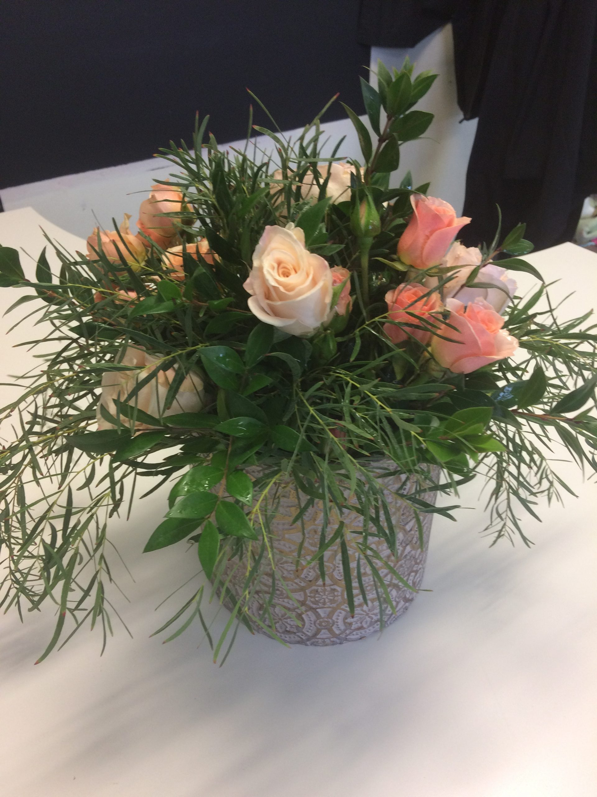Pink and peach coloured roses with ruscus and rosemary in shabby chic ceramic vase