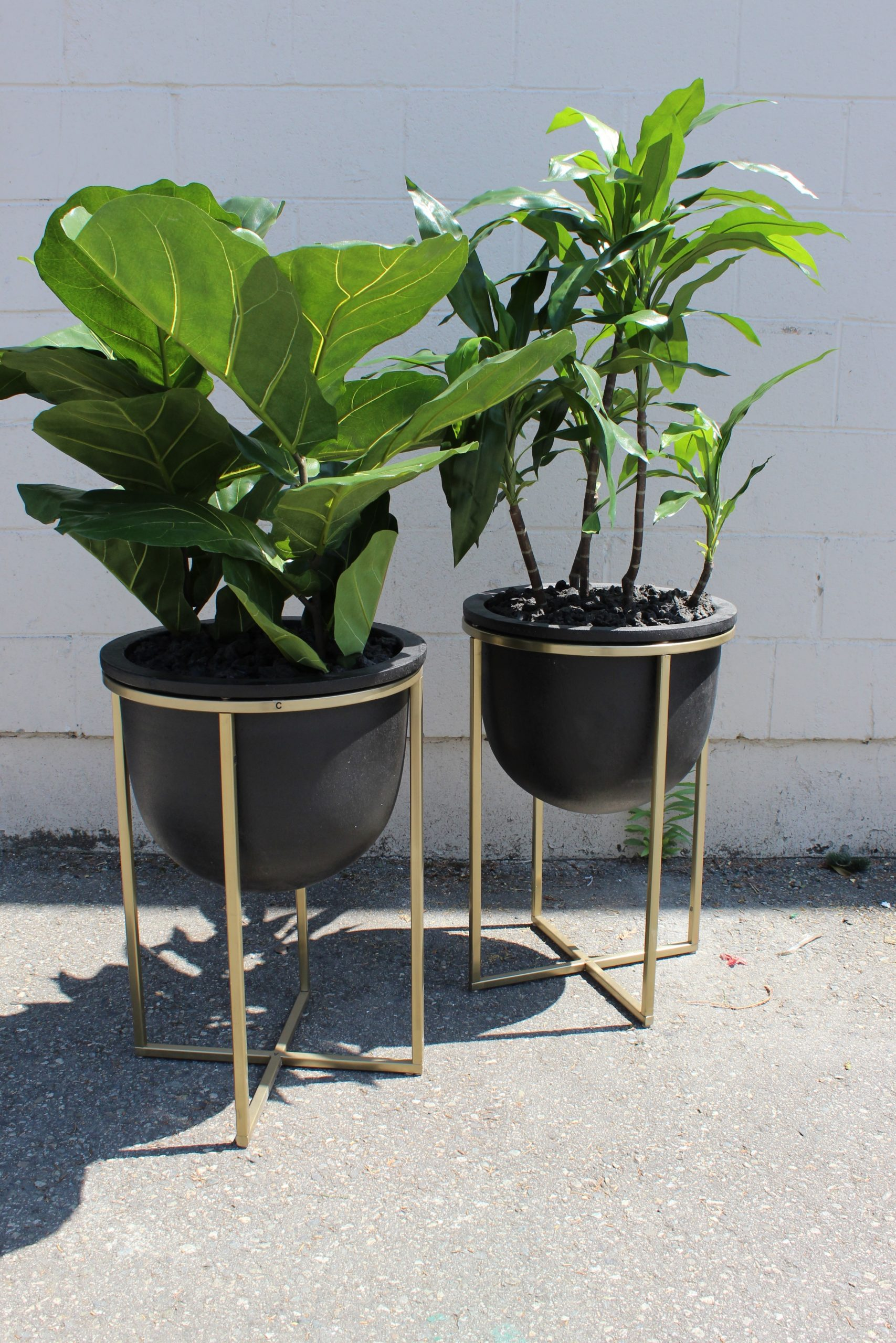 Black and gold contemporary planter and planter stands with artificial fiddle leaf and dracaena plants for restaurant decor
