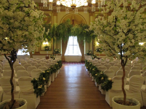 White cherry blossom trees flanking aisle entrance, with two canopy willow trees on natural trunk at alter