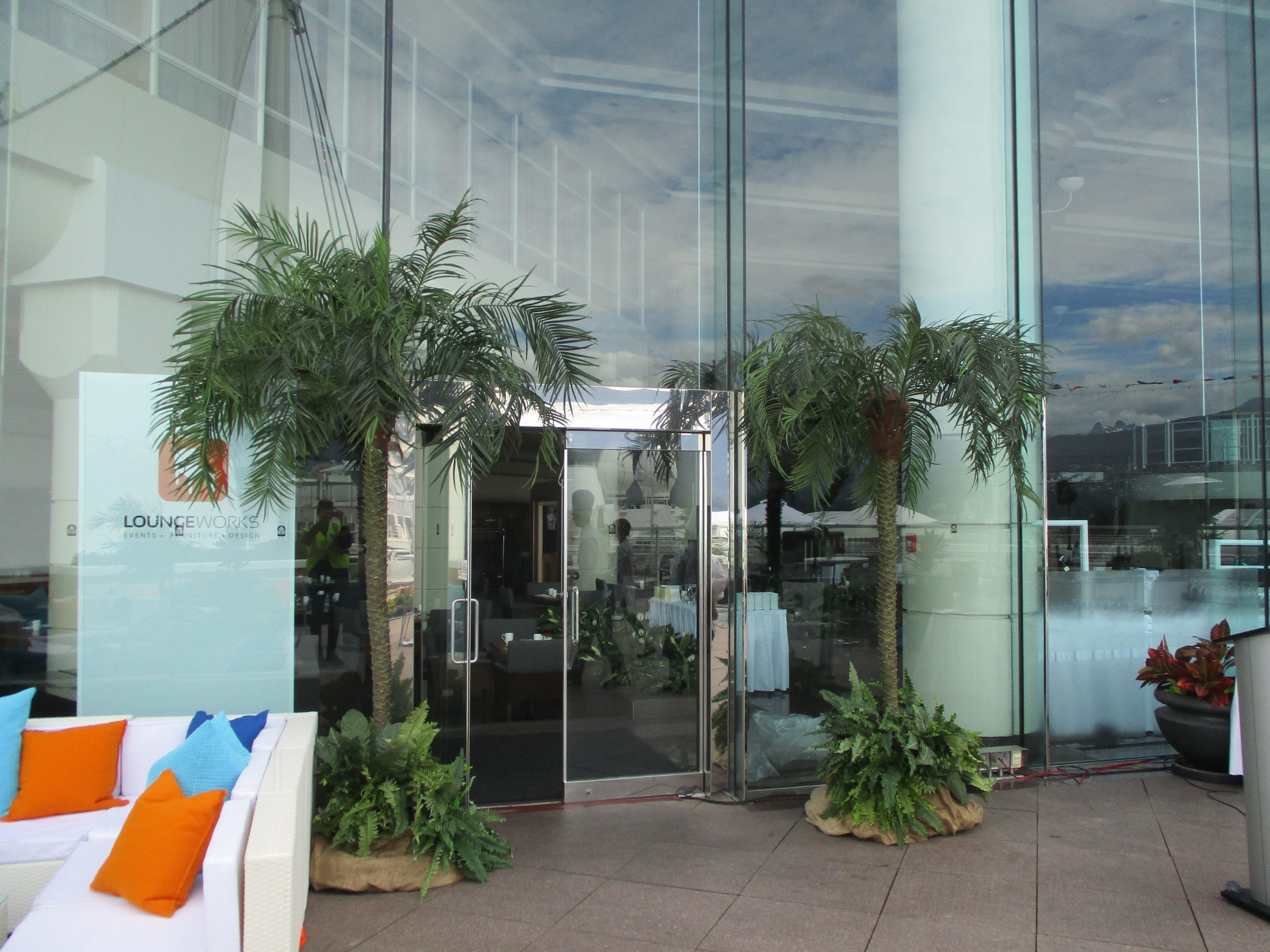 Two tall phoenix palm trees with tropical base gardens flanking door entrance for event