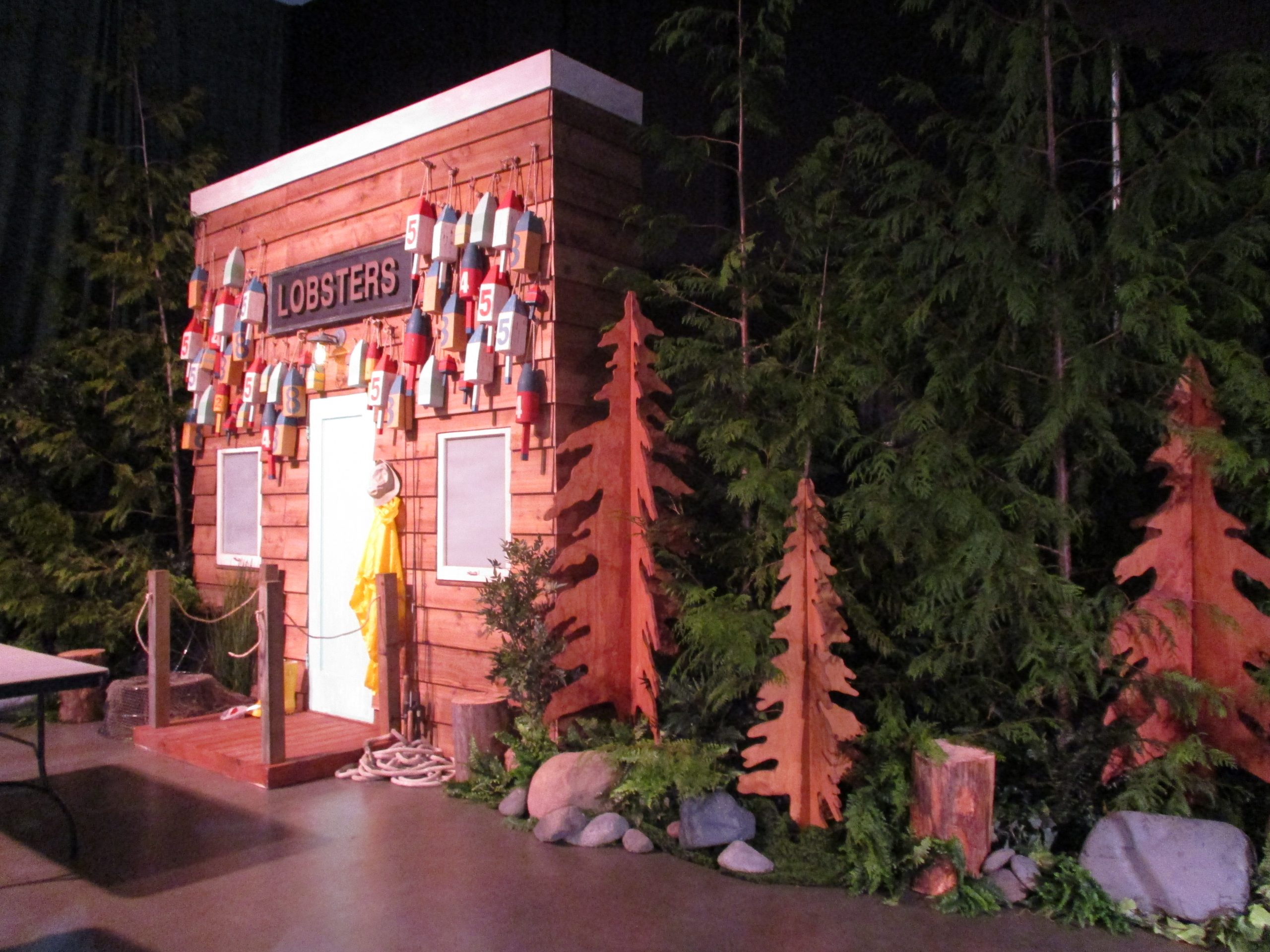 Live evergreen vignette for life like woodsy display with cabin props and wood cut out trees by client