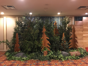 All live evergreen tree vignette with added wood cut out tree props by client