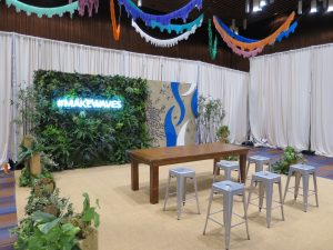 Custom backdrop and photo op featuring artificial green wall with holes to put live potted plants and a land and sea theme