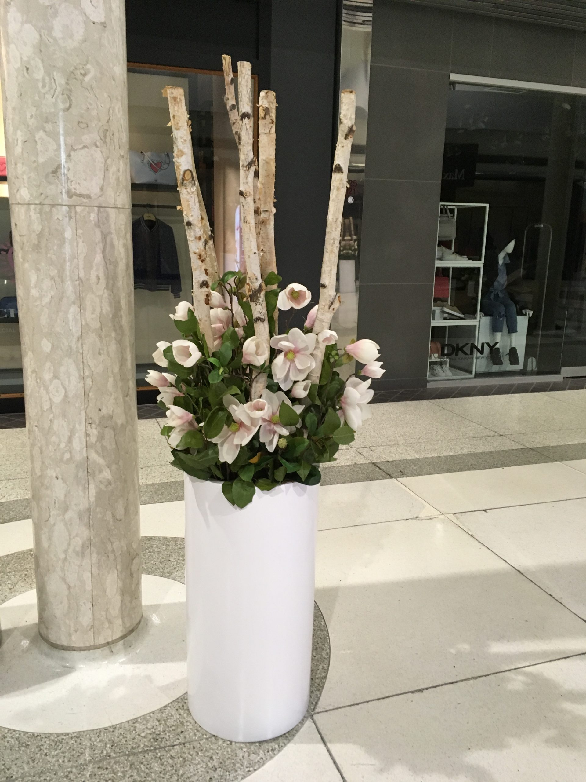 Large Cylinder white fibreglass planter with natural birch poles, artificial magnolia stems and salal for Mother's Day setup
