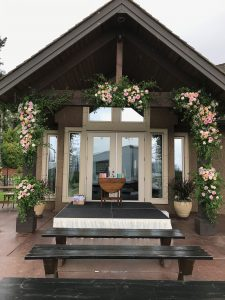 Clients at-home, built-in arbour, accented by large floral cages filled with fresh pink and peach roses and italian ruscus