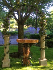 Greystone arch with ivy and wisteria alter with tree cookie table