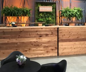 Uber Event Bar backdrop made of preserved moss panels in wood frame and base, with large live potted ferns on bar backs and client provided custom signage