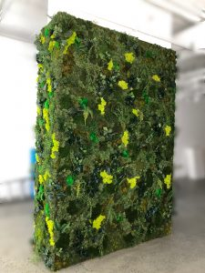 Preserved moss panel with artificial greenery accents creating a pillar wrap for retail space