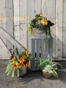 Succulent and marigold and yellow flower arrangements in various pots and containers set on wood crates for easter and spring time decor